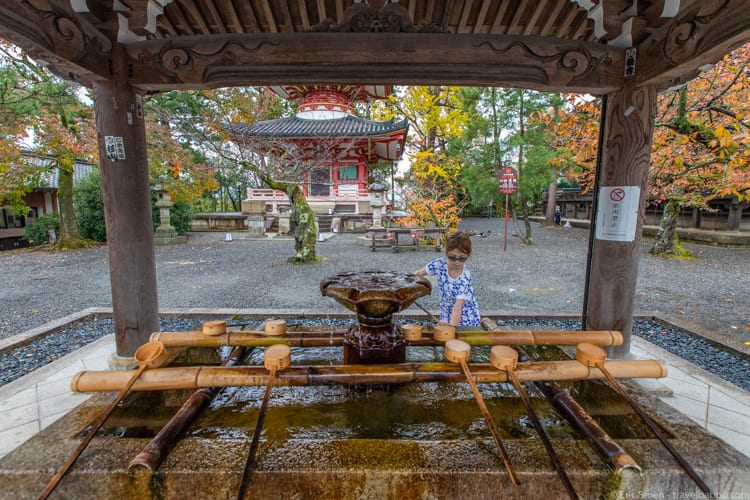 Kyoto with kids - My daughter washing her hands at a Chionin Temple purification fountain